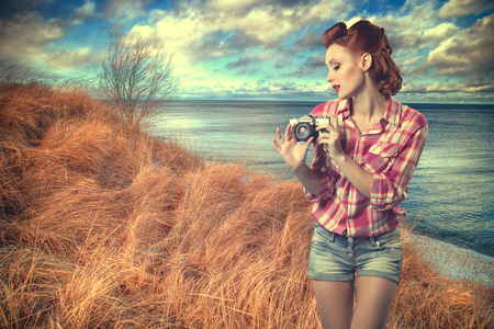 despite: pin-up with a camera. Sexy redhead woman near the sea despite the weather photographs on camera nature. vintage retro Stock Photo