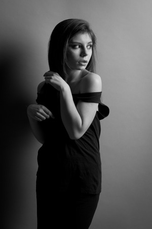 black and white photo. Beautiful caucasian brunette woman with long shiny brown hair and clean skin. Portrait of a fashion model in studio photo