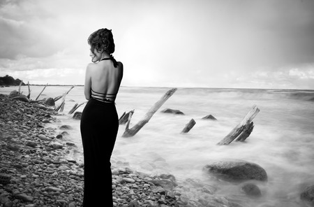 woman is standing with his back to the coast. Dramatic black and white portrait