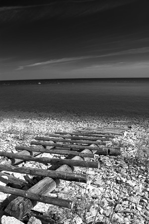 black and white photography. sea and the horizon and the sand and rocks and stairs photo
