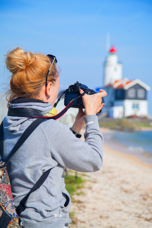 marken: Girl shoots video at the lighthouse on the sea. In the Netherlands in the summer at the village Marken