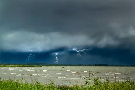 Blitz auf dem Meer. Vorhänge an der Küste. regnerisches Wetter