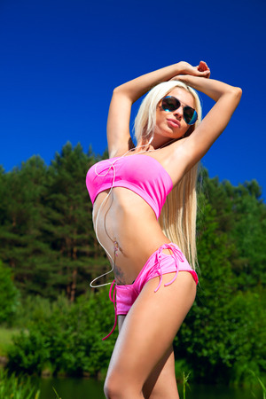 arched neck: blonde in a pink bikini girl sunbathing, listening to music. Wearing sunglasses Stock Photo