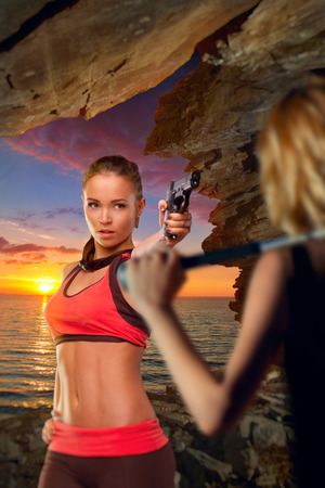 girl action: Girl with a pistol in a cave by the sea at sunset is protected from girl with a bat. in search of adventure