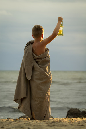 translation of boy dressed in clothing of the ancient Greek time. It should be on the beach