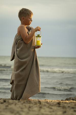 be dressed in: translation of boy dressed in clothing of the ancient Greek time. It should be on the beach