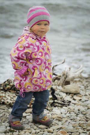 hypersensitivity: Girl in the autumn at the sea . walking on rocks in the ocean background