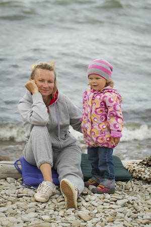 urban parenting: mother and daughter at the sea in the fall sitting around the campfire .
