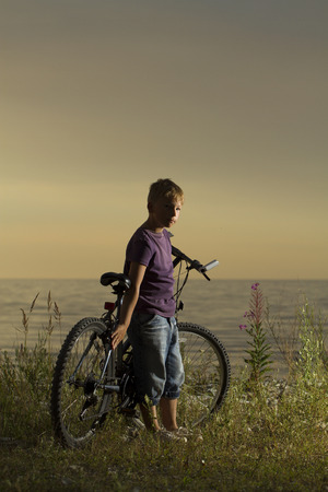 one wheel bike: boy on a bicycle near the sea in the evening at sunset. summer vacation Stock Photo