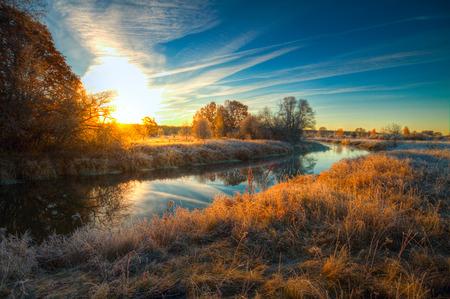 Dawn bij de rivier .osen. vorst op bomen en gras Stockfoto