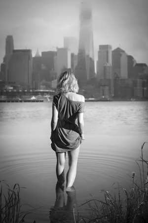 photography backdrop: girl in the evening into the Hudson comes against the backdrop of Manhattan. Black and white photography