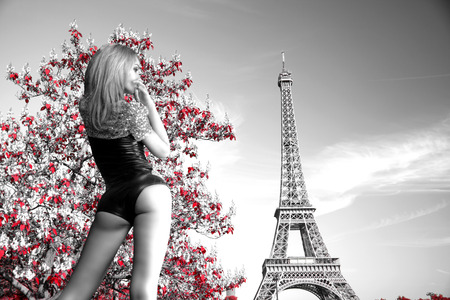 girl in a body on the background of the Eiffel Tower. black and white photo with the color red