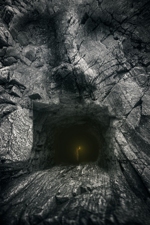 eyes cave: boy goes to the cave in the form of the face. Adventure Stock Photo