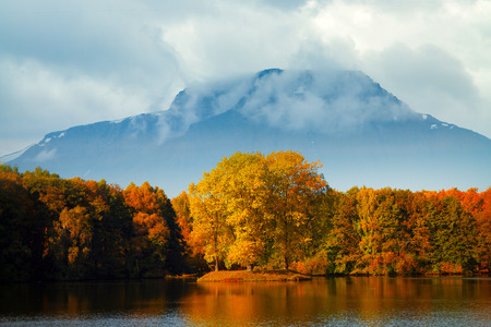 ridge of wave: Golden Autumn at the lake on a background of mountains. Stock Photo
