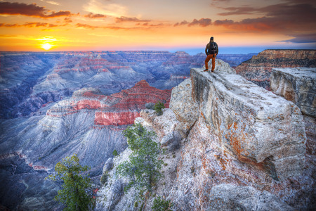 mochila de viaje: hombre en el Gran Cañón al amanecer. turística en América