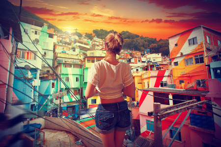 woman mountain: Brazilian woman standing in the favela, and admires the sunset in Rio Stock Photo