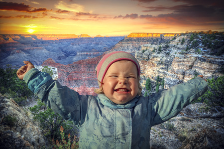 grand child: girl queen of the Grand Canyon, USA. child arms outstretched to the sides of joy.