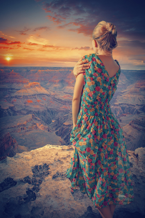 Woman in dress stands in the Grand Canyon. enjoying the sunset. vintage style photo