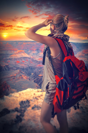 Woman travels to the Grand Canyon with a backpack. enjoying the sunset photo