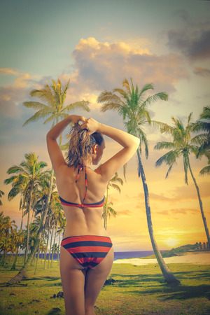girl in a swimsuit standing on the beach looking at Easter Island ocean and the sunset photo