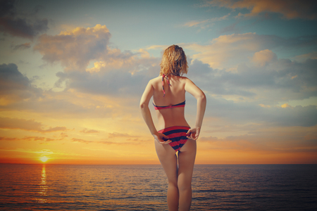 girl in a swimsuit standing near the sea at sunset. beach holiday photo
