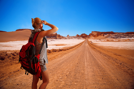 girl tourist with a backpack. Amphitheatre is beautiful geological formation of Moon Valley in Atacama Desert, Chile
