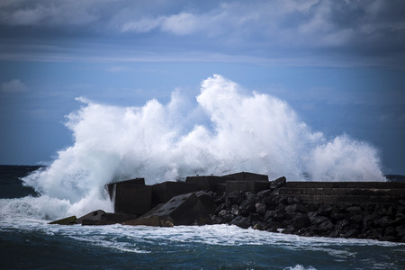 breakwater: Stone breakwater with breaking waves. Europe