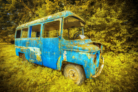 rusty old blue bus standing in the woods Stock Photo