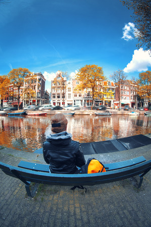 dutch girl: girl stands near the river and looks at the streets of Amsterdam. early autumn