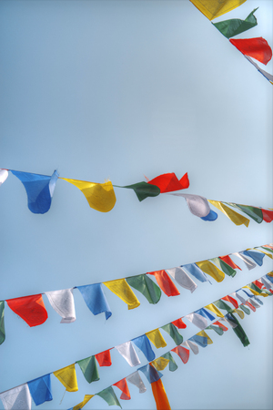Many colorful waving prayer flags suspended between trees