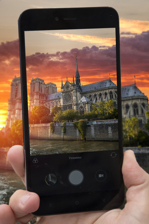 videobloger takes pictures on a smartphone sunset Notre Dame de Paris. France. Europe 写真素材