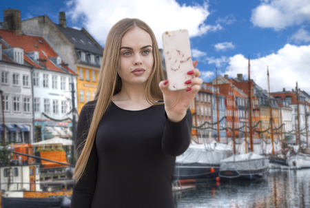girl blogger shoots on a smartphone in the Nyhavn is the old harbor of Copenhagen. Denmark