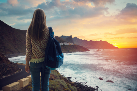 girl with a backpack looking at the city on the coast at sunset