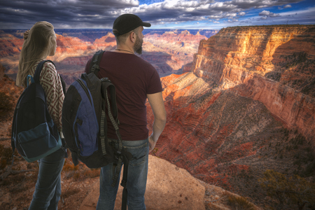 girl with a male traveler stands with backpacks on the background of the Grand Canyon, USA