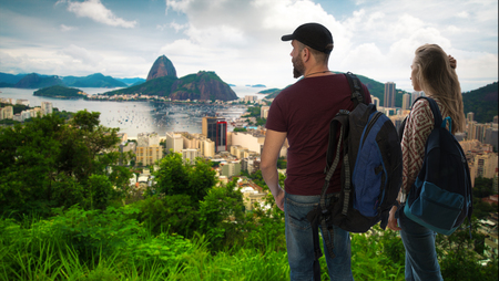 girl with a man travelers is standing with backpacks on the background of RIO Stok Fotoğraf