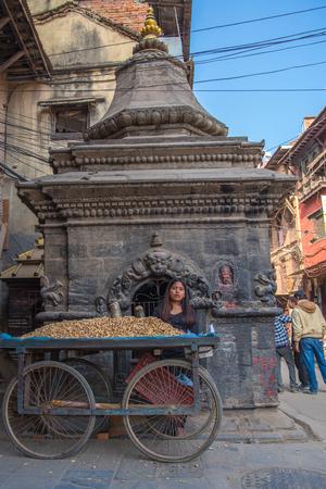 BHAKTAPUR, NEPAL - DECEMBER 14, 2017: A girl in Durbar Square is trading nuts, Kathmandu