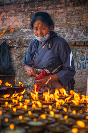 KATMANDU, NEPAL - DECEMBER 19, 2017: A woman is standing at a table with candles in the street, Kathmandu Editorial