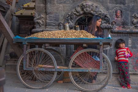 BHAKTAPUR, NEPAL - DECEMBER 14, 2017: Two children in Durbar Square are selling nuts, Kathmandu