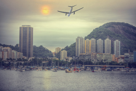 the plane is flying over Rio De Janeiro, Brazil . View of the city through the bay Stock Photo
