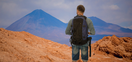the traveler is standing with a backpack. San Pedro de Atacama, Chile, South America Archivio Fotografico