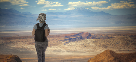 a tourist girl is traveling with a backpack in the Atacama Desert.