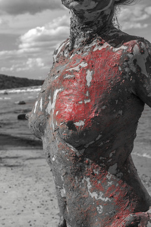 a woman's smeared with mud on the background of the sea