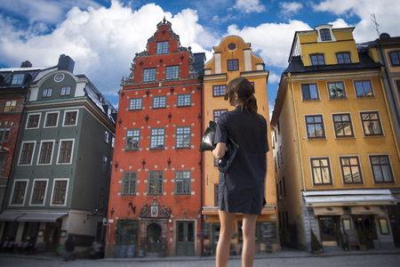 a woman stands in the background of the houses of Stockholm. Sweden.