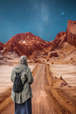 A woman in a hijab travels through the desert.
