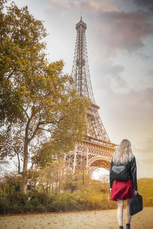The girl in the red skirt goes against the background of the Eiffel Tower. Paris.