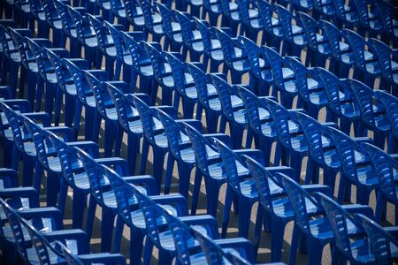 empty blue chairs stand on the street for a concert.