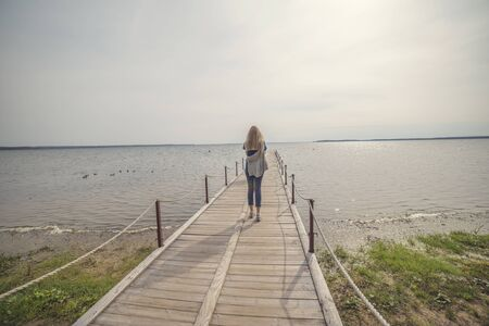 girl walks along the pier on the lake