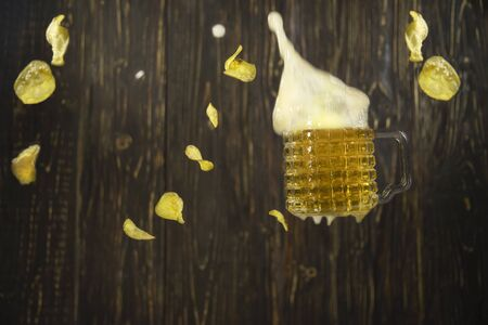 Falling beer and chips on a wooden wall background. Levitating food.