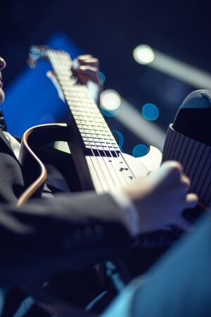 The artist plays the guitar. Rock band at a concert