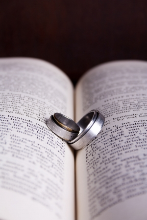 Two rings with Hebrew verses in the shape of a heart on an open Afrikaans Bible photo